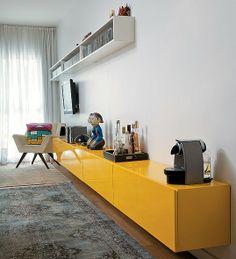 """Com 4,50 m de comprimento, o móvel amarelo de laca dá a sensação de amplitude à sala estreita. """"Ele dá apoio às salas de jantar e de estar, ..."""