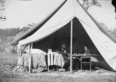 Abraham Lincoln meets with a Civil War general under a tent. Photo by Matthew Brady.