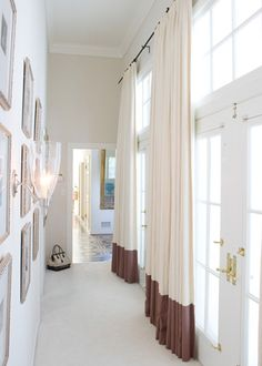 source: Blumenfeld Interiors    Elegant foyer with a wall of French doors and transom windows dressed with floor length ivory drapes banded with a mauve border, two-tone curtains. Opposite the light filled wall hangs a framed gallery wall lit by polished nickel and glass sconces. Light walls, tall ceilings and cream carpeting keep the foyer hall light and airy.