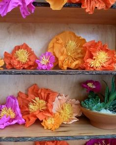 Oversize tissue-paper flowers in desert shades lined shelves for a bright backdrop at Kate Bosworth's wedding welcome party.