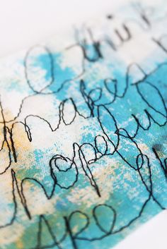Paint fabric then use sewing machine free stitching for script and designs. Clever!