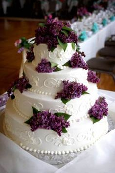 Very elegant four tier buttercream wedding cake decorated buttercream icing swirls and purple flowers.