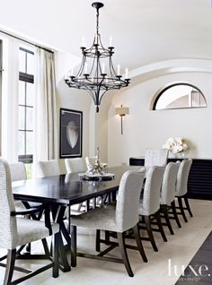 In this #glamorous dining room a Dessin Fournir #chandelier from David Sutherland hangs above a #custom Dessin Fournir #table and Holly Hunt #chairs.. #Luxe