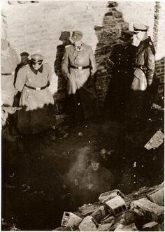 SS Major General Jürgen Stroop (center), accompanied by SS and police officers, looks on as SS soldiers uncover the entrance to an underground bunker during the suppression of the Warsaw ghetto uprising. The original German caption reads: They were also discovered in underground bunkers. Photo credit: Glowna Komisja Badania Zbrodni Przeciwko Narodowi Polskiemu, Polish National Archives