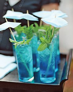 """Blue mojitos garnished with mint sprigs and blue paper """"eyelet"""" umbrellas"""