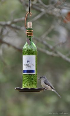 the garden-roof coop: DIY Wine Bottle Bird-Feeders. Drill holes in the side of the bottle to allow the seeds to fall out onto the nifty, thrift store plate that's been glued to the bottom.