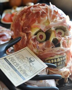 The Food: Meat Head Platter  To make this grisly visage, top right, begin with a clean plastic skeleton head—Stefanie popped hers off a full-size model. Then drape alternating slices of prosciutto and ham—ask the deli counter to slice it extra-thin—across the skull until all of the plastic is concealed. (The cold cuts will stick on their own.) Nestle half a pimiento-filled olive into each eye socket and add a label supported by a plastic jewelry display hand (find one at JewelryBeadsAndFinding