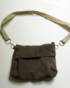 "Roll down your leather shirtsleeve, cut it off, and sew a purse.Project Materials:  Leather or suede shirt, $5 @thrift store  4 rings (about 1"" in diameter), 2 lanyard hooks  Leather sewing machine needle  Thread, sewing machine, on hand"