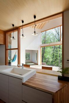 Japanese house featuring a kitchen that offers views of a surrounding forest.