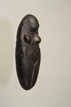 Upper Paleolithic Female Figurine, Eastern Europe, ca. 12,000 BCE carved from black steatite. The abdomen is swollen indicating pregnancy with wide hips and buttocks. Subtle features such as belly button are present along with engraved hair. Remains of red ocher.