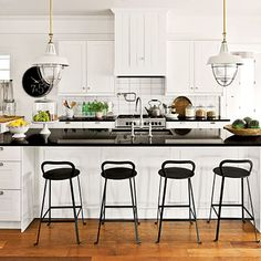 Farmhouse Kitchen | The main working part of the kitchen lines up front to back with twin cabinets capping both island ends and flanking the range. | SouthernLiving.com