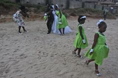 Two flower girls walk off as a photographer takes a photo of a wedding party at sunset on a beach outside of Accra, Ghana, on May 26. (Jon Gambrell/Associated Press)