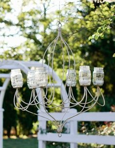 Mason jar chandeliers hung from nearby trees, adding a rustic, whimsical flair to the decor. As the sun set, the chandeliers gave off a soft, warm glow and had the appearance of floating in thin air.