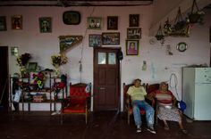 Carmen Amelia and Pedro Pablo rest in the main room of their home on San Cristobal, in the Galapagos Islands. The photos on the wall give a glimpse into their long marriage. Carolyn Van Houten/reesenews