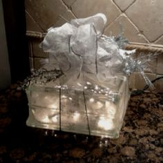 Opaque glass shower block with twinkle lights.  Drill a hole in the block large enough to insert a small strand of twinkle lights. Add decorations as desired.