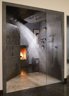 Double shower heads and a fireplace.