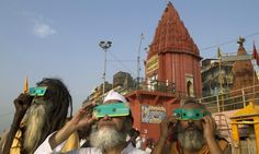 Hindu holy men on the banks of the Ganges River in Varanasi, India, use special cardboard eclipse glasses to watch the transit of Venus Wednesday.