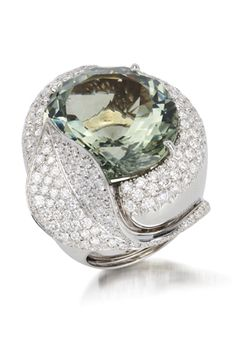 An 18K white gold ring, set with a green Amethyst stone, adorned with diamonds around.
