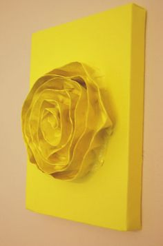 Fold painter's tape in half so it sticks to itself, form into the shape of a flower, stick it to canvas, and paint.
