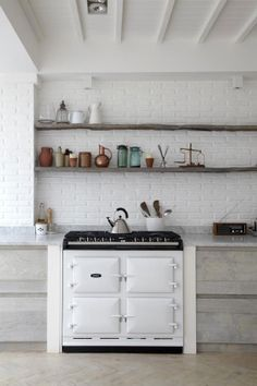 White brick wall kitchen, wood burning stove, open concept wooden shelves, copper accents