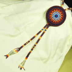 "This beaded Bolo Tie is Native American hand made. The long stem is peyote stitch.   Materials: Size 13 Charlotte Cut Glass Bead, Bugle Beads, Commercially Tanned Leather Tribe: Navajo Size: 47"" L Overall (Including fringes), Fully Beaded Length 24"" L Each Side (Including fringes),  The medallion is 3 1/3"""