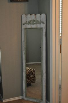 Cheap,regular 'ol, full length mirror~paint mirror edges~ old fence pickets and glue-on wood embellishment~magic!