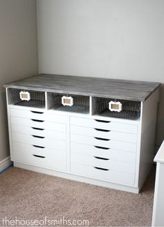 Custom built around two Ikea drawer units. Love the baskets and framed tags!