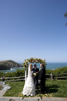 A couple exchanges vows on an oceanfront lawn.