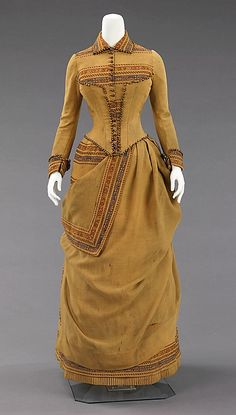 Ensemble, 1885  The unusual color and intriguing use of solid and striped wool fabric in this day dress has a folkloric aesthetic, which may have been inspired by an Amelia Hollenback's travels through the Southwest. The inventive asymmetrical draping shows a high level of sophistication and design sensibility that was atypical for a day dress.