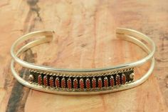 Genuine Red Coral set in Sterling Silver Bracelet. Beautiful Needle Point Design. Created by Zuni Artist Sharon Hustito. Signed by the artist. The Zuni Pueblo is located in New Mexico, Land of Enchantment.