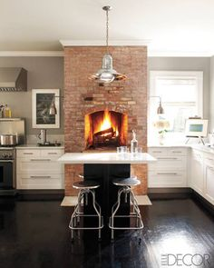Sconces by Visual Comfort flank the original fireplace in the kitchen, and the light fixture is a flea market find.