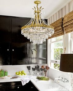 Black kitchen cabinets with bamboo shades and crystal chandelier.