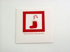 Christmas Bootie - This soft and gentle white folded card has a distinctive felt texture inside and out. Conveying both warmth and high quality. The design features two candy canes in a handmade crocheted Christmas bootie which is mounted to the white square and poppy red square. This card comes with white envelope in protective cellobag. - Size: 135x135mm - Greeting on the front: Merry christmas & a happy new year -   Inside greeting: none