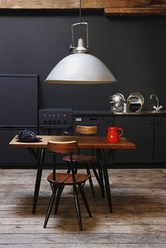 Rustic modern black kitchen - love the table and floors!