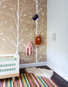 Tree-motif wallpaper and a striped rug in a child's room