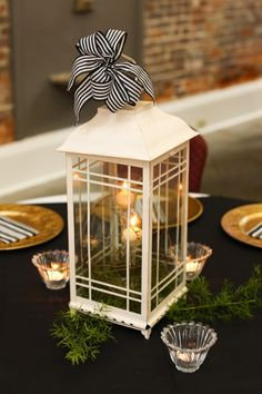 Beautiful classic ... candles inside lantern atop greenery as centerpiece.