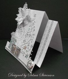 "silver and white design paper was put on the two side panels and a piece of white on white, large polka dot, paper attached to the center section.  The beautiful Memory Box ""Flowering Christmas Tree"" was die cut using a sparkly silver paper.  The boxes were created with two different silver papers.  It is just a square cut then a piece cut for the lid - very simple to do.  The bow on the box to the left was die cut three times and the bow on the smaller box die cut twice.  I love these Memory Bo"