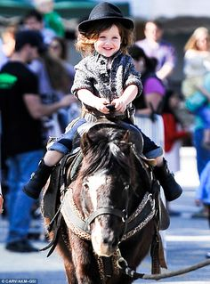 Filled with glee: The stylish tot smiled as he experienced being on top of the animal