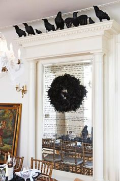 A murder of crows... fake crows crown an elaborate mirror marked with a spooky poem. Their feathers make up a wreath.