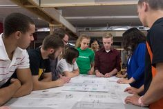Members of the Solar Decathlon team examine plans for the project.