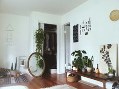 painting of plants placed with real pants on bench and mirror on floor