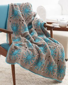 Worked in motifs and featuring gorgeous pop color details, this crocheted blanket is a great way to brighten up your home.
