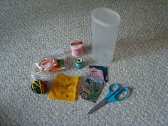 Sewing kit contains scissors, thread, ball of yarn, fabric patches, needles and safely pins securely pinned onto felt square and ziplock bag containing elastic, ribbon and buttons.  All of this fits into a plastic Crystal Light drink container.