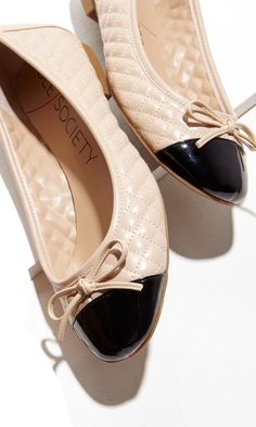 Quilted ballet flat with a delicate bow and cap toe.