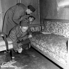 With only candles to light their way, war correspondents examine a couch stained with blood located inside Hitler's bunker.