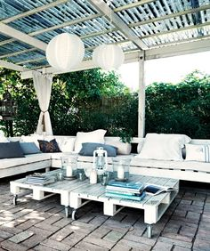 outdoor patio on a budget. furniture made of pallets topped with cushions add pillows and some cheap paper lanterns to make it look rustic chic.....i will definitely try this in my next place!