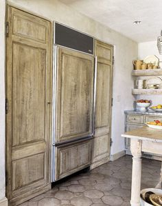 could you cover any refrigerator / freezer in wood?  How about using vintage hardware to make it look like an old fashioned ice box?