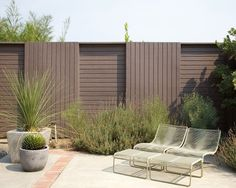 Brown wooden #privacy #fence with #vertical and #horizontal slat #design.  Love those #lounge #chairs and #shrubs for an arid-looking #climate. Gorg!