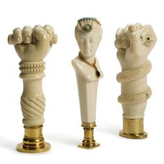 Three Carved Ivory and Silver-gilt Desk Seals, 2nd half 19th century, one carved in the form of a female bust wearing gold jewelry set with gold and garnet, the matrix with monogram, another carved as a fist holding a baton, the matrix carved with an elaborate coat of arms, the last with a fist holding a serpent with emerald glass eyes, the base carved with a coat of arms.