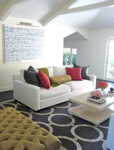 fun, eclectic living room design with navy blue chain link rug, white modern sofa, glossy white lacquer modern cocktail table, green velvet tufted rectangular storage ottoman, gray & red pillows and art.